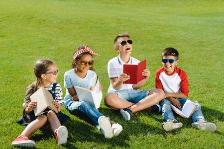 Children reading books in park
