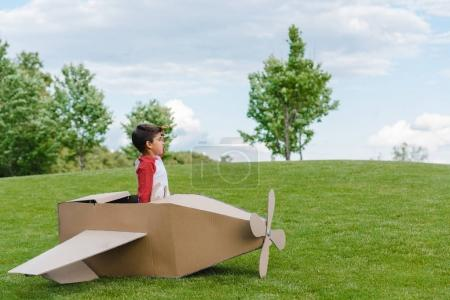 Boy sitting in cardboard plane
