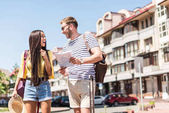 Multiethnic couple of tourists with map