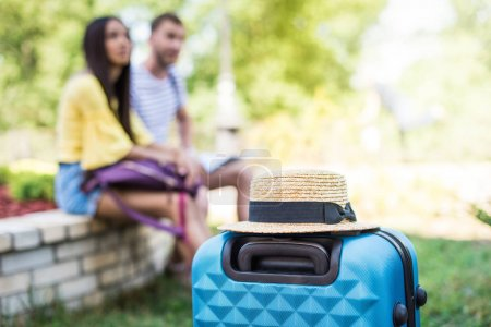 Photo for Close-up view of suitcase with straw hat and couple of travelers sitting behind - Royalty Free Image
