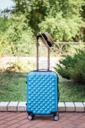 Photo pour Vue rapprochée de la valise bleue avec chapeau de paille debout sur la chaussée dans le parc - image libre de droit