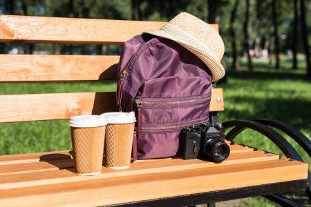 Photo pour Vue rapprochée du sac à dos avec chapeau de paille, appareil photo et papier tasses sur un banc en bois dans le parc - image libre de droit