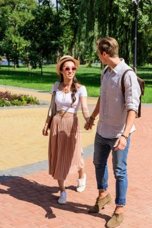 multicultural couple walking in park