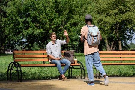 man waving to friend in park