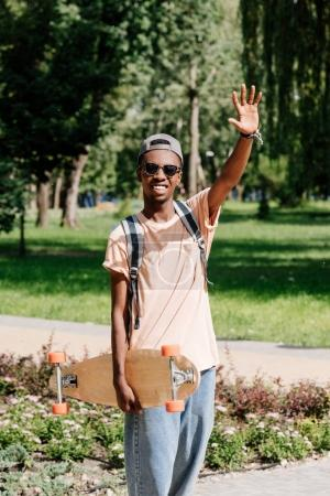 Photo for Stylish african american man with outstretched arm holding longboard - Royalty Free Image