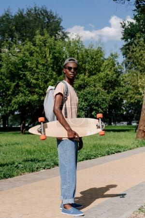 Photo for Stylish african american man holding longboard in park - Royalty Free Image