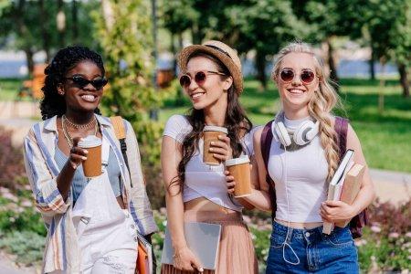 Photo pour Heureuses femmes multiculturelles avec des tasses jetables de café dans les mains marchant dans le parc - image libre de droit