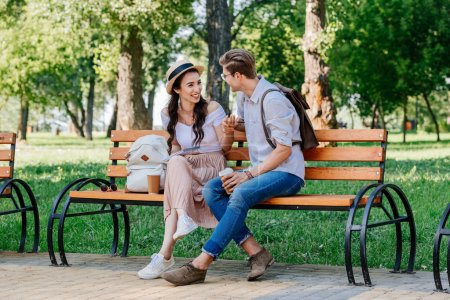 Photo for Happy multicultural couple having conversation while sitting on bench - Royalty Free Image