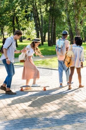 multiethnic friends walking in park