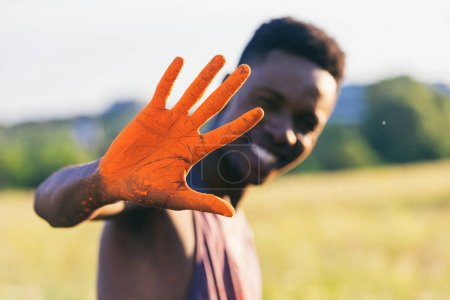 Photo for Selective focus of african american man showing hand in orange paint at holi festival - Royalty Free Image