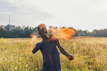 Photo pour Portrait de heureux homme afro-américain jetant de la poudre colorée au festival holi - image libre de droit
