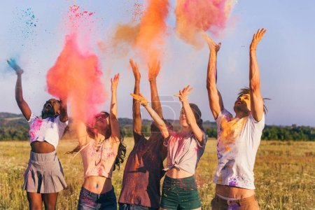 Photo for Multicultural friends throwing colorful powder at holi festival - Royalty Free Image