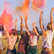 Multicultural friends throwing colorful powder at ...