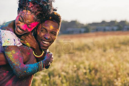 Photo for Portrait of happy african american couple piggybacking at holi festival - Royalty Free Image