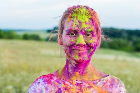 Photo for Portrait of smiling woman with colorful paint on face during holi festival - Royalty Free Image