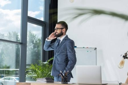 businessman talking on smartphone at workplace