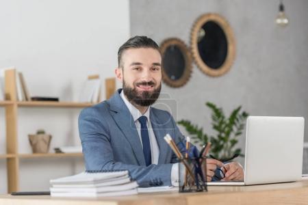 Foto de Retrato de hombre de negocios sonriente mirando la cámara en el lugar de trabajo con el ordenador portátil - Imagen libre de derechos