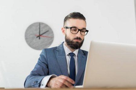 Photo pour Portrait d'homme d'affaires ciblée sur écran d'ordinateur portable au lieu de travail au bureau - image libre de droit