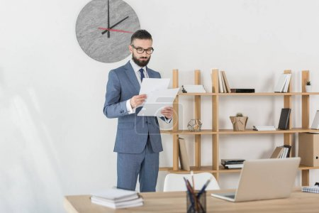 Photo for Focused businessman in grey suit analyzing documents in modern office - Royalty Free Image