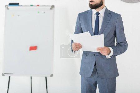 Photo pour Vue partielle de l'homme d'affaires détenant les papiers en mains au bureau - image libre de droit