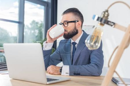 businessman drinking coffee at workplace