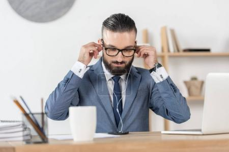 businessman in earphones at workplace
