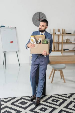 Photo for Fired sad businessman with cardboard box in hands standing at workplace in office - Royalty Free Image