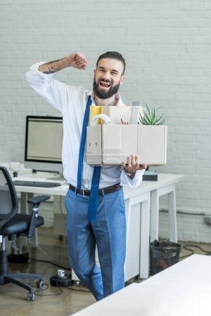 excited fired businessman with box