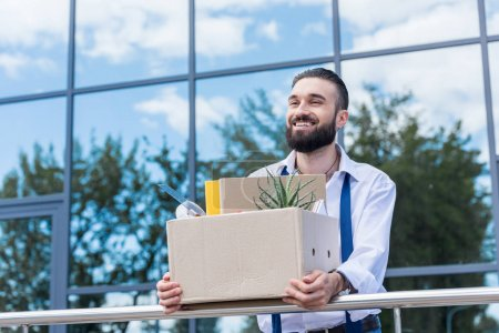 fired happy businessman with cardboard box