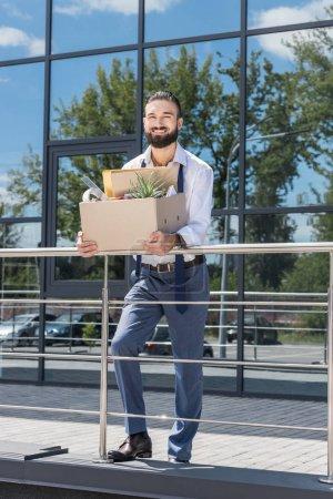 fired happy businessman with cardboard box