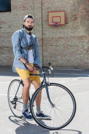Photo for Hipster man sitting on bicycle and looking at camera on street - Royalty Free Image