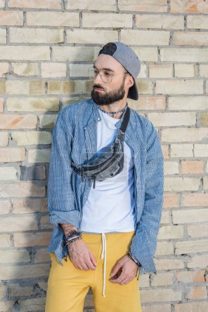 Photo for Portrait of pensive hipster man in cap leaning on brick wall on street - Royalty Free Image