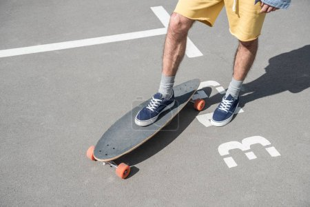 man standing on longboard