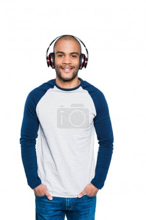 Photo for Happy young african american man listening music in headphones and smiling at camera isolated on white - Royalty Free Image