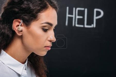 Photo pour Jolie femme brunette avec appareil auditif, avec le mot aide sur tableau noir - image libre de droit