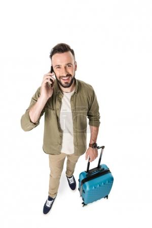 man with suitcase talking on smartphone