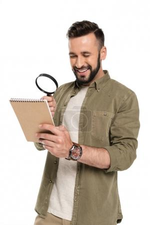 man with magnifying glass and notebook