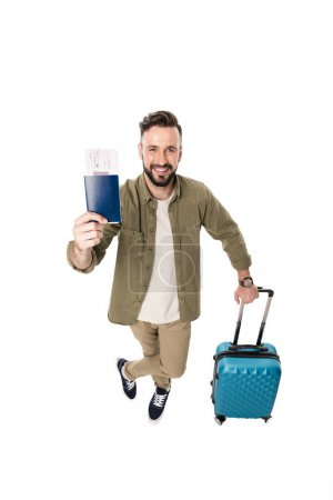 Photo for Smiling man with suitcase holding passport and ticket in hand isolated on white - Royalty Free Image