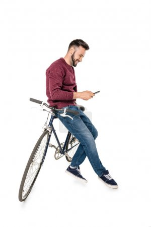 Photo for Side view of young smiling man using smartphone while leaning on bicycle isolated on white - Royalty Free Image