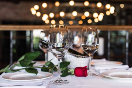 Photo pour Vue rapprochée de la belle fleur de rose rouge avec du vin à table au restaurant - image libre de droit