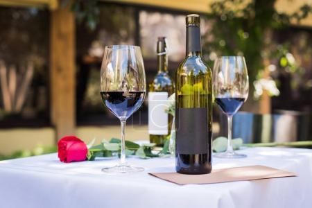 Foto de Vista de primer plano de bella flor rosa roja con el vino en la mesa en el restaurante - Imagen libre de derechos
