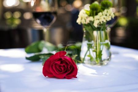 Photo for Close-up view of beautiful red rose flower with wine at table in restaurant - Royalty Free Image