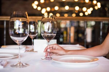 Photo for Cropped view of young woman holding glass of white wine in restaurant - Royalty Free Image