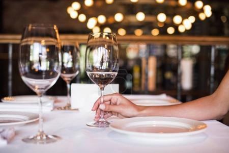 Photo pour Recadrée vue de jeune femme tenant le verre de vin blanc au restaurant - image libre de droit