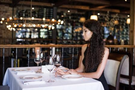 Photo for Portrait of young beautiful woman sitting at table in restaurant, having white wine - Royalty Free Image