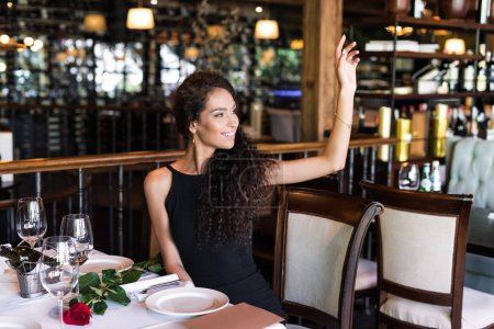 woman with raised hand in restaurant