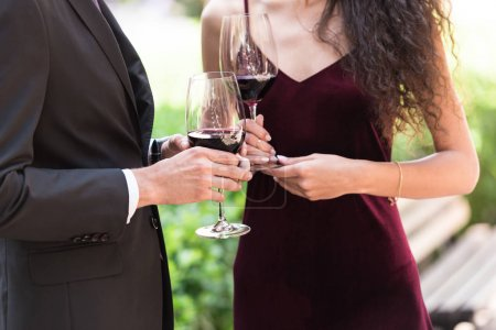 Couple standing with wine in garden