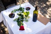 Rose flower with wine at table in restaurant