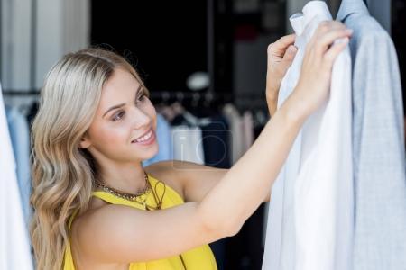 woman choosing shirt in store