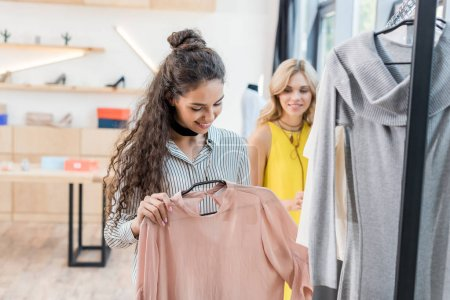 Photo for Two young shopaholic women choosing clothes in showroom - Royalty Free Image